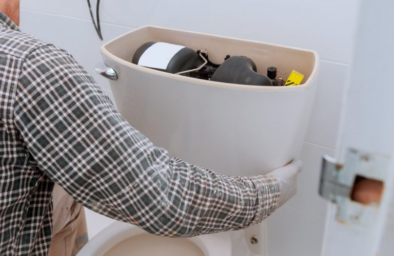 Repairing man working with toilet tank in bathroom, closeup