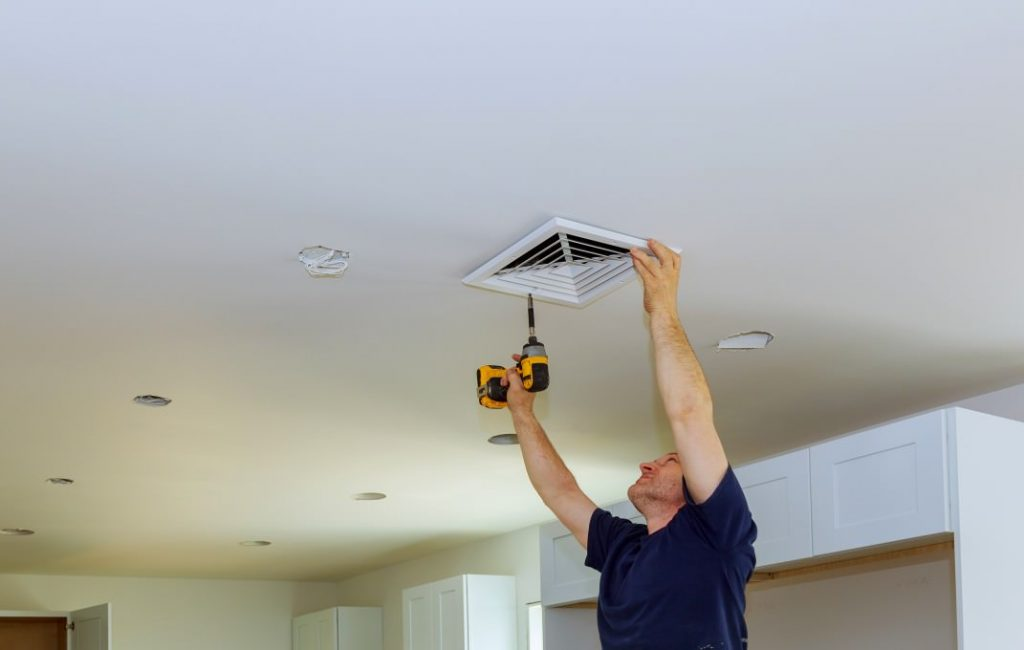 worker-builder-installing-air-conditioner-ventilation-cover-construction-of-building