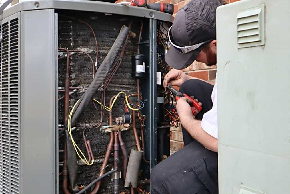 Service repair being done on a heat pump hvac system