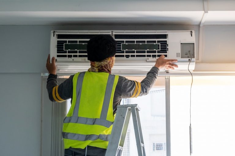 Young Man technician maintenance air conditioner indoors. Cleaning, Washing and Conditioning Service concept