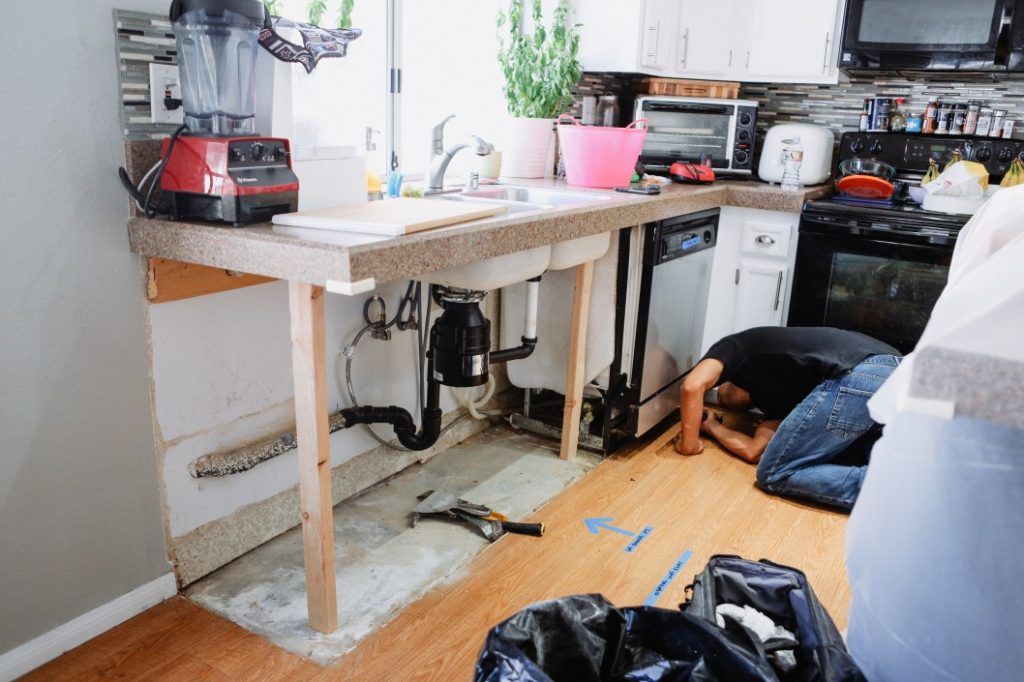 Plumber contractor making repairs to a home kitchen remodel