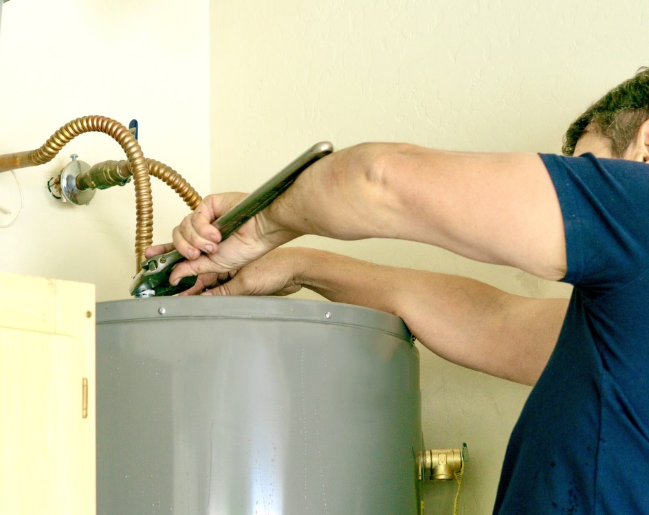 plumber using a wrench to make adjustments on top of a hot water heater